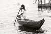 Girl poling a dugout canoe BW, Tahas River, Kampong Phluk, Cambodia
