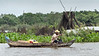 Man-in-dugout-canoe-on-Tonle-Sap-during-monsoon-season-with-fish-traps-in-the-water-hyanciths,-Cambodia