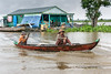Rainy-day-during-monsoon-season-on-Tonle-Sap-with-dugout-canoe-and-houseboat,-Cambodia
