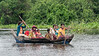 Dugout-canoe-full-of-women-and-children-on-the-Tahas-River,-Tonle-Sap,-Cambodia