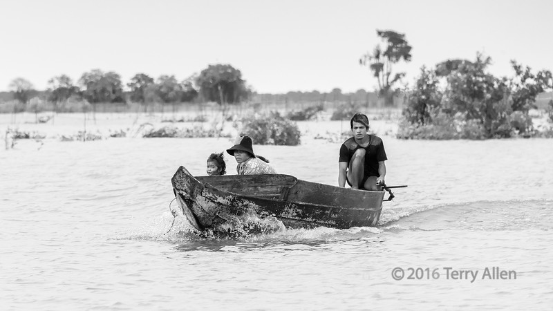 Family-in-boat-during-monsoon-season-on-Tonle-Sap,-Cambodia