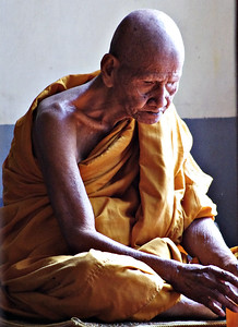 Older Monk Eating Alone