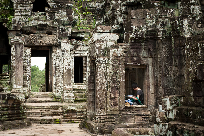 A young girls sits and reads, Angkor Wat, Cambodia