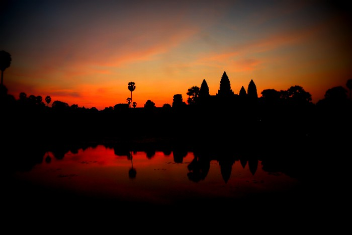 A fiery orange sunset with wisps of pink and blue in Angkor Wat, Cambodia.