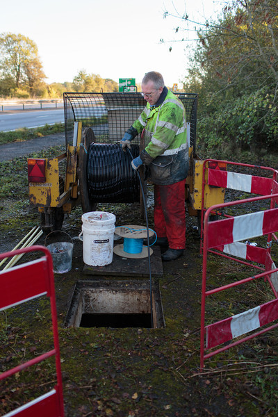 He opens the chamber next to the A14. The cable (which will contain the thinner optic-fibre cable) is fed manually along the BT ducts (10 November 2013). For more information, visit http://www.increasebroadbandspeed.co.uk/cambridgeshire