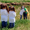 Shantel, left, and sister Kaeann Bright, watch their mother Lori hug a close friend, Margie Haas, while picking up trash. The girls are the nieces of John Breaux.<br /> Dozens of people picked up trash around Louisville to celebrate the John Breaux Clean-Up Day on Saturday.<br /> Cliff Grassmick / May 9, 2009