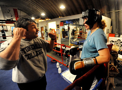 Trainer Dave Gaudette tells Tawnia Wormell where her hands should be during instruction at the Front Range Boxing Academy in Boulder. For  more photos and a video of Tawnia, go to www.dailycamera.com. Cliff Grassmick / November 12, 2009