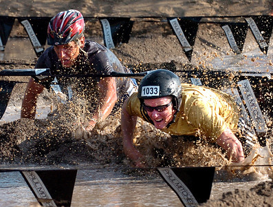 Andy Call, left, and his brother, Matt, work through the mud pit of the Muddy Buddy race. The Muddy Buddy Ride and Run requires a 2-person team to finish a 6-7 mile course with 5 obstacles. One member will ride and one will run, but they need to finish together. The race was held at the Boulder Reservoir on Sunday.  For more photos and a video, go to www.dailycamera.com.   Cliff Grassmick / August 16, 2009