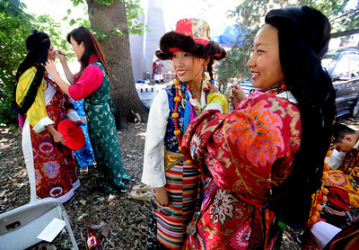 "Phuntsok Dolkar, center, and Tenzin Yuthok, prepare their costumes for the dance performance. Boulder celebrated the 7th annual World Tibet Day in Central Park. The City of Boulder also declared the day as  ""Dalai Lama and Tibet Awareness Day.""  Cliff Grassmick / July 11, 2009"