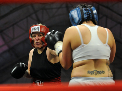 Tawnia Wormell, left, 42,  throws a punch at Rachel Griego in her first professional fight on November 6th at the Softball Country arena in Denver. For more photos and a video of Tawnia, go to www.dailycamera.com. Cliff Grassmick / November 12, 2009