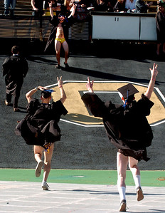 Robert Craig and Brian Robertson, both members of the CU water polo team, run up to greet teammate Josh Zeldner before graduation. About 5,280 degrees were conferred Friday  during the 2009 University of Colorado Spring Commencement at Folsom Field. Cliff Grassmick / May 8, 2009