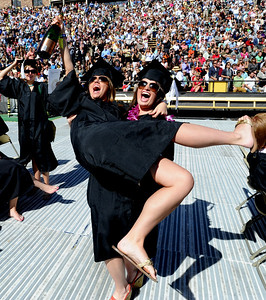 Kristen Jorgensen picks up friend Megan Burns during the celebration of getting their bachelor's degrees. About 5,280 degrees were conferred Friday  during the 2009 University of Colorado Spring Commencement at Folsom Field. Cliff Grassmick / May 8, 2009