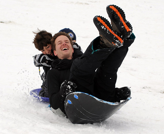 "Grant Besser and his sons, Cole, left, and Carson, hidden, appear to be loosing control on another run down the hill.<br /> It was another big sledding day at Scott Carpenter Park on Sunday.<br /> For more sledding photos, go to  <a href=""http://www.dailycamera.com"">http://www.dailycamera.com</a>.<br /> Cliff Grassmick / November 15, 2009"