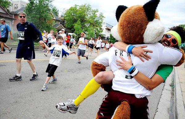 Jon Fidge, of Boulder, is hugged by a mascot after finishing the 31st annual Bolder Boulder 10K road race on Memorial Day, May 25, 2009 in Boulder, Colorado. This year's race saw it's one millionth participant, and had over over 50,000 register.<br /> KASIA BROUSSALIAN /CAMERA
