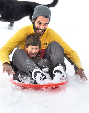 N0113SNOW.JPG N0113SNOW.JPG N0113SNOW<br /> Ysmael Reyes and his son, Marcelo, 5, of Boulder, ride their sled down the hill at Scott Carpenter Park on Monday morning.<br /> cq all<br /> Photo by Marty Caivano / January 12, 2008