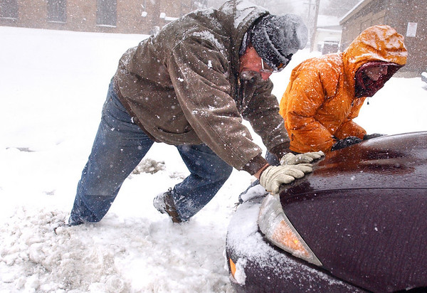 SNOW4444.JPG Wes Lints, at left and Shane Grigsby work to free a car stuck in a snowstorm in Boulder, Colo. Thursday morning.<br /> Photo by Paul Aiken / The Camera / March 26, 2009