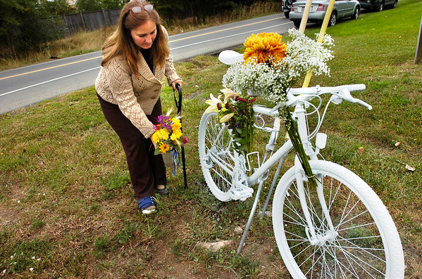 BIKE.JPG Connie Flynn leaves flowers on a white bike set in memory of Casey Najera on the side of the intersection of Violet Avenue and 28th Street in Boulder on Wednesday September 23, 2009. Najera was killed on Sunday while riding his bike. Flynn was longtime friends of Najera and his family.<br /> Photo Paul Aiken / The Camera / SEPTEMBER 23, 2009.