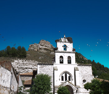 La Iglesia de Santa María in Belorado, with storks in the tower and caves built into the rock behind.
