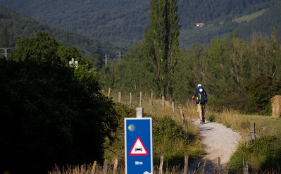 A pilgrim on the Camino de Santiago continues on the path to Larrosoaña after crossing the highway, with blue sign indicating caution.