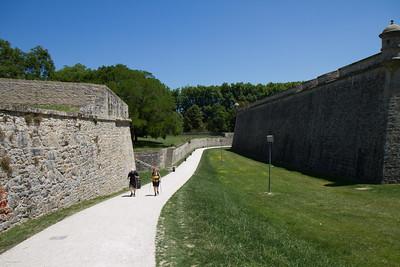 Pilgrims walk along the medieval city walls of Pamplona on the Camino de Santiago.