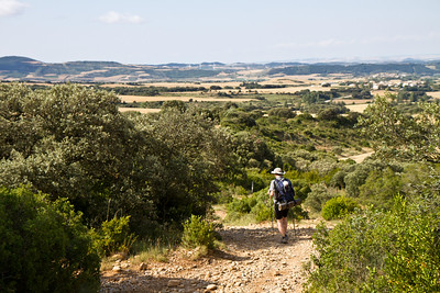 A pilgrim rounds the corner as he descends from Alto de Perdón toward the town of Uterga on the Camino de Santiago.