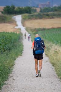 Pilgrims walk the plains between Cizur Menor and Alto de Perdon on the Camino de Santiago.