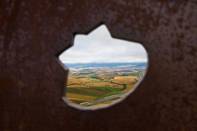 A view back toward Pamplona through a shell-shaped opening the the pilgrim statue at Alto de Perdon on the Camino de Santiago.