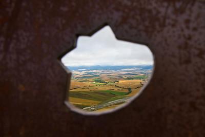 A view back toward Pamplona through a shell-shaped opening the the pilgrim statue at Alto de Perdon on the Camino de Santiago.