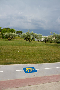 The Camino de Santiago leaves Pamplona through parks and university campus on paved paths marked with the yellow shell symbol.