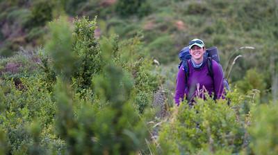 Author Anna Dintaman walks through fields of scrub brush toward Alto de Perdón on the Camino de Santiago.