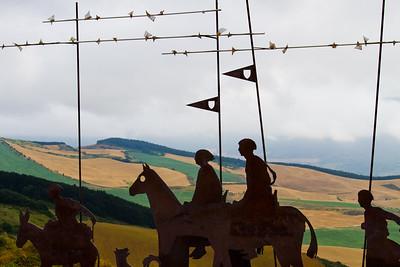 A statue of medieval pilgrims stands at Alto de Perdón, the former site of a pilgrim church and hospice.