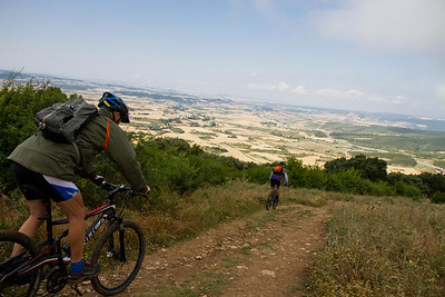 Bicycle pilgrims ride down from the Alto de Perdón on the Camino de Santiago.
