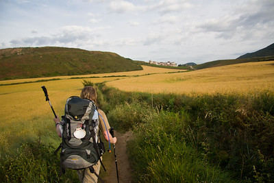 A pigrim with a traditional shell on her backpack walks through the countryside of Navarra on the Camino de Santiago.