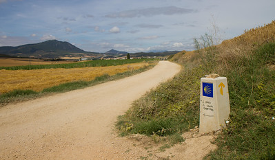 A cement waymarker points down the dusty path to Lorca.