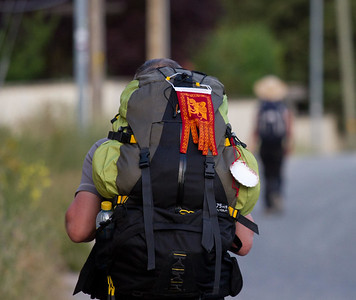 A pilgrim bears his heavy backpack on the Camino de Santiago, near Puente la Reina.