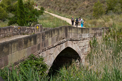 Pilgrims cross a medieval bridge over the Río Salado on the Camino de Santiago.