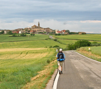 A hiker approaches the medieval town of Sansol on the Camino de Santiago.
