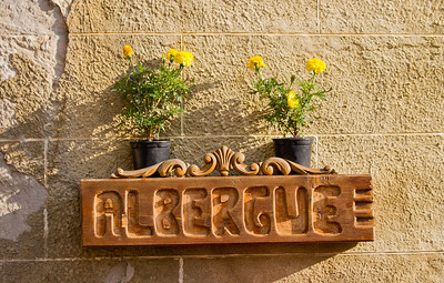 A wooden sign marks the entrance to the albergue in the town of Sansol.