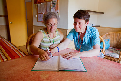 Volunteer hospitaleras at the parochial albergue in Viana look through the guest book.