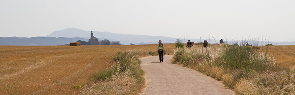 A hiker enjoys the wide flat path between Torres del Río and Sansol.