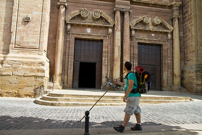 A pilgrim looks up at the doors to Iglesia de la Asunción in Navarrete, Spain.