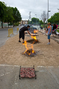 Locals in Nájera prepare fires to cook meat on for a celebration.