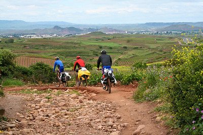 Colorful bicyclists disappear around a turn on the Camino de Santiago.