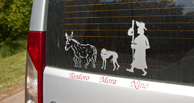 Pilgrim stickers adorn a vehicle parked along the Camino de Santiago.