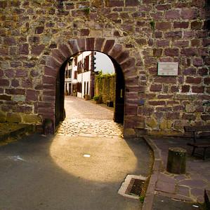 """Pilgrims leave St-Jean-Pied-de-Port on the Camino de Santiago through Porte Saint Jacque,  """"St. James door."""""""
