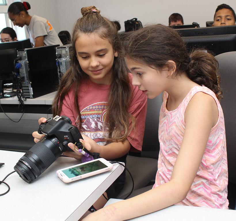 girls examining camera