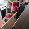 Emma playing the piano in the train lobby