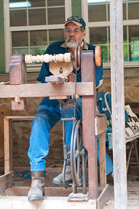 Man demonstrating how to use a leg-powered lathe.