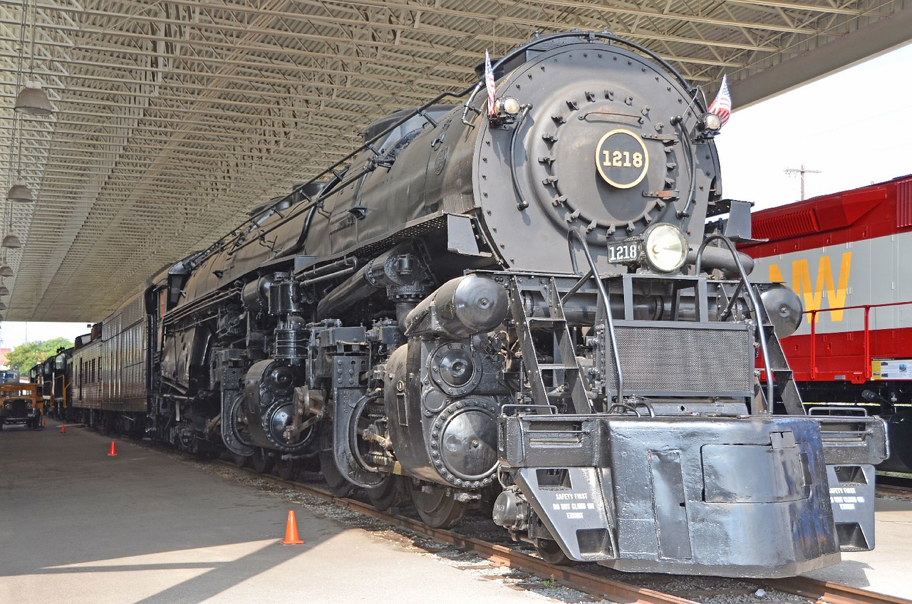 "4639 – One of the two stars of the exhibit. The ""A"" class #1218. Powerful enough to pull the largest freights, fast enough to pull the longest passenger trains at 80mph all day. Frightful, to stand next to it, it's main wheels taller than I am, and think of it moving past at that speed. Designed and  built by the Norfolk and Western railroad,  in it's own shops, just down line about a mile from the museum. One of the finest steam locomotives ever built."