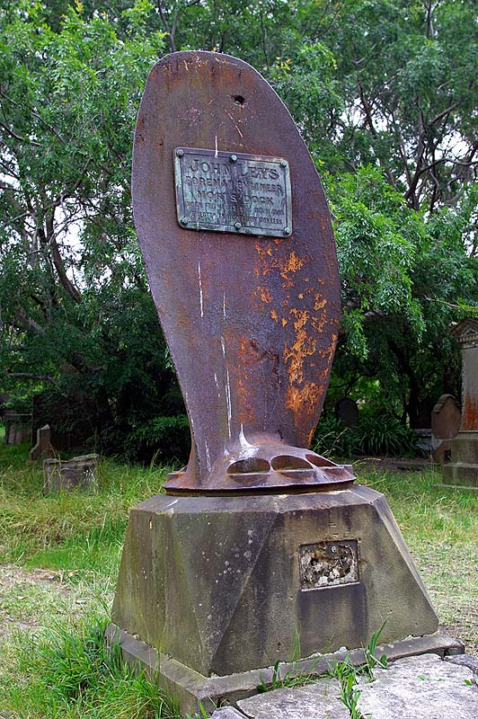 A steel ship's propeller stands tall above the grave.